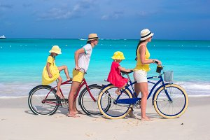 Young parents and kids riding bicycles on a tropical white sand beach