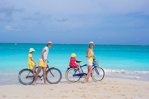 Young parents and little girls with bikes on a tropical white sandy beach
