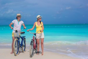Young happy pair riding bikes on white tropical beach