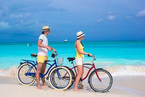 Young happy couple riding bikes on white tropical beach