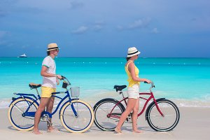 Young happy couple riding bikes on white sandy beach