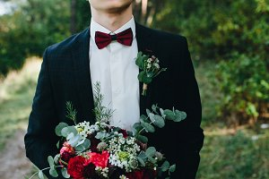 groom holds bouquet