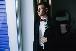 groom standing at the window