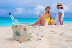 Bottle of wine and two glasses background happy couple at beach
