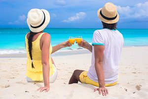 Happy couple with two glasses of orange juice on beach vacation