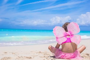 Cute little girl with butterfly wings on beach vacation