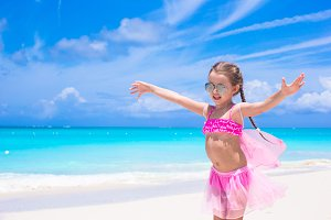 Funny little girl have fun on beach summer vacation