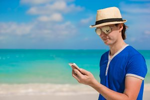 Young happy man with his phone on beach vacation