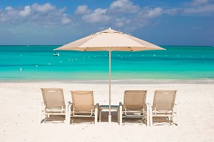 White umbrellas and sunbeds at tropical beach