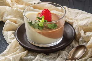 Italian dessert. Chocolate and vanilla panna cotta with mint and raspberry. Dark wood background. Fabric milky.