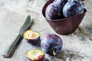 Ripe plums scattered on a gray wooden background. Bio healthy fruits. Selective focus. Copy space background