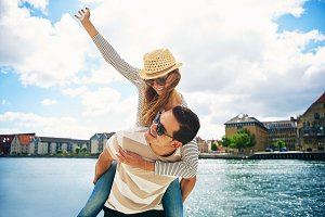 Fun loving young couple frolicking at a waterfront