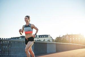 Smiling female athlete running along city bridge