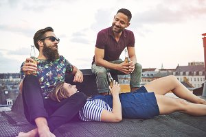 Woman in lap of bearded man near friend on roof