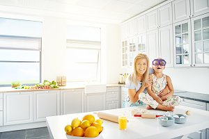 Laughing mother and daughter together in kitchen