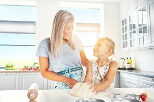 Happy young mother and daughter baking