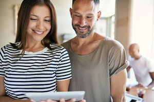 Smiling couple hold computer tablet between them