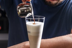 Barista is pouring coffee in milk