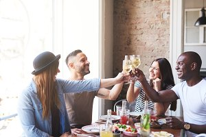 Two mixed couples celebrating with drinks at table
