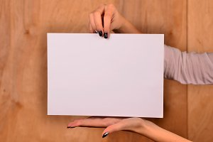 Hands of a caucasian female upholding blank sheet of paper with copy-space for your text