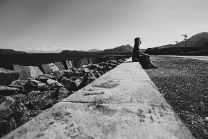 girl in profile sitting on a stone