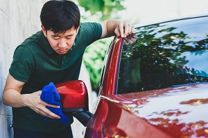 Young Asian man in uniform cleaning and washing a car in outdoor