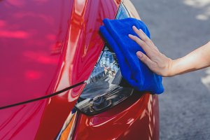 Young man washing and wiping a car in the outdoor