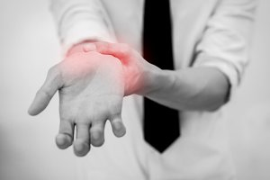 Office Man touching painful wrist. Pain in a man wrist.