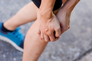 Runner touching painful knee. Athlete runner training accident. Sport running knee sprain.
