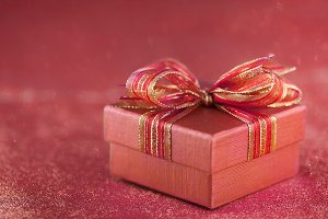 red gift box on glitter red background