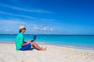 Young man working on laptop at tropical beach
