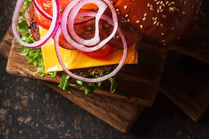 Closeup of home made beef burgers with lettuce and mayonnaise served on little wooden cutting board. Dark background.
