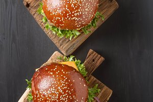 Closeup of home made beef burgers with lettuce and mayonnaise served on little wooden cutting board. Dark background. Top view