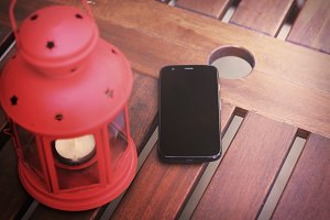 Smartphone and lantern on table