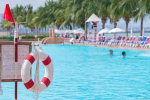 red lifebuoy near swimming pool.
