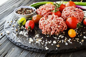 raw minced meat, vegetables with salt and spices, selective focus