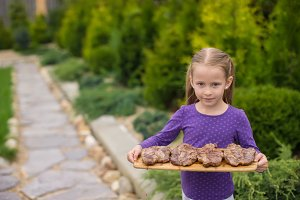 Adorable girl with grilled steaks