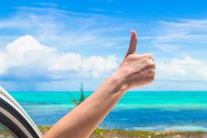 Young woman showing thumbs up on the beach