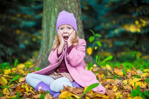 Little happy girl in autumn park