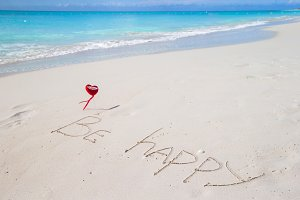 Be happy written in a sandy tropical beach