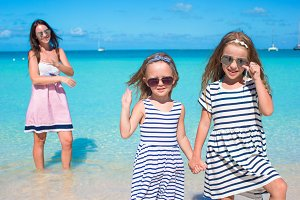 Happy girls and young mom during beach vacation