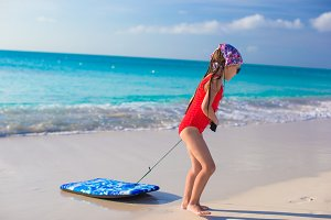 Little adorable girl pulls a surfboard on white shore