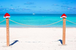 Two Santa hats on fence at tropical white beach