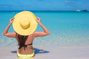 Woman sitting in yellow hat on white sand beach enjoying summer vacation