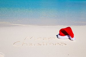 Santa Hat on white sandy beach and Merry Christmas written in the sand