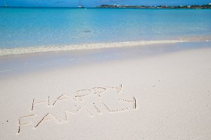 Happy family written on tropical beach white sand