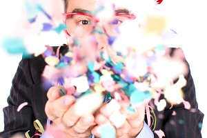 Young man blowing confetti