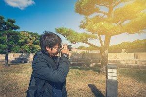 Asian man taking photo in Garden