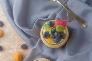 Milk Caramel dessert in a glass jar with berries. Bright stone background, blue cloth. Top view