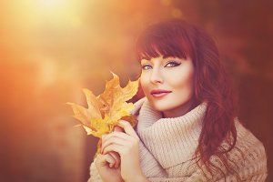 Beautiful girl outdoors with autumn leaves